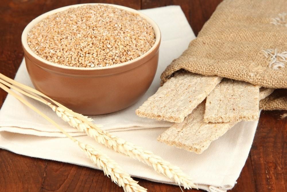 зерно с миске и рядом пшеничный колос и хлебцы