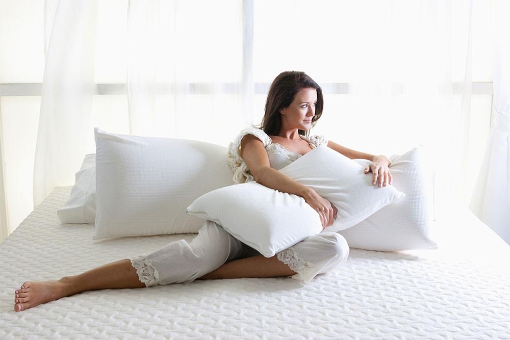 белый матрас с подушками и девушка на нём