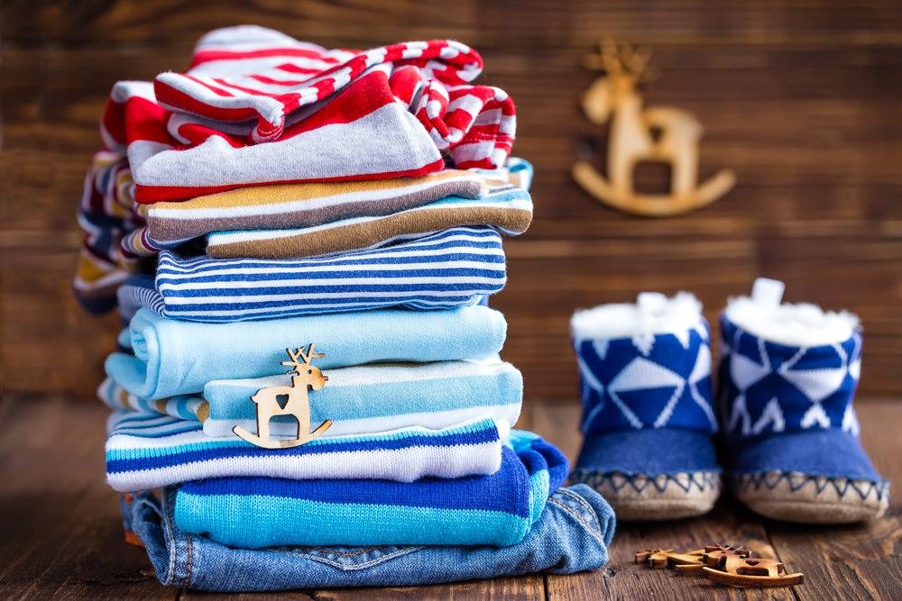 Стопка детской одежды на деревянном столе