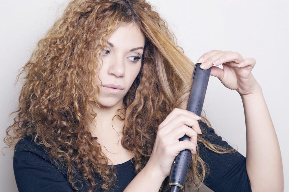 девушка выпрямляет вьющиеся волосы