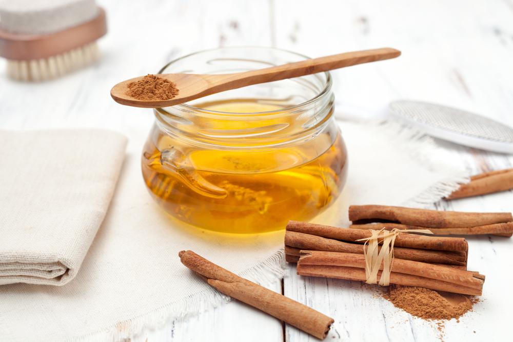 мед в стеклянной банке и корица на белом столе
