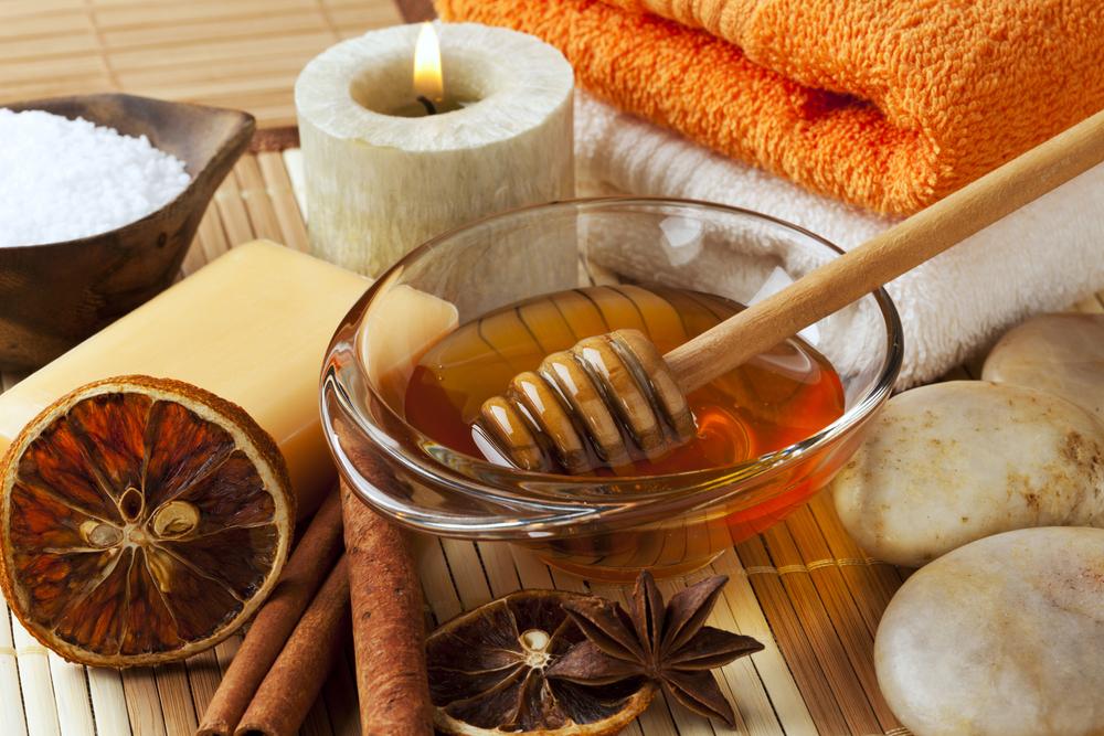 мёд в миске и корица на столе вместе с полотенцами