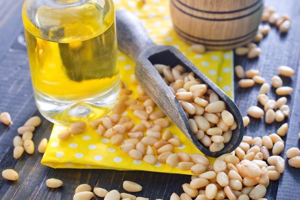 кедровые орешки на столе с баночкой масла