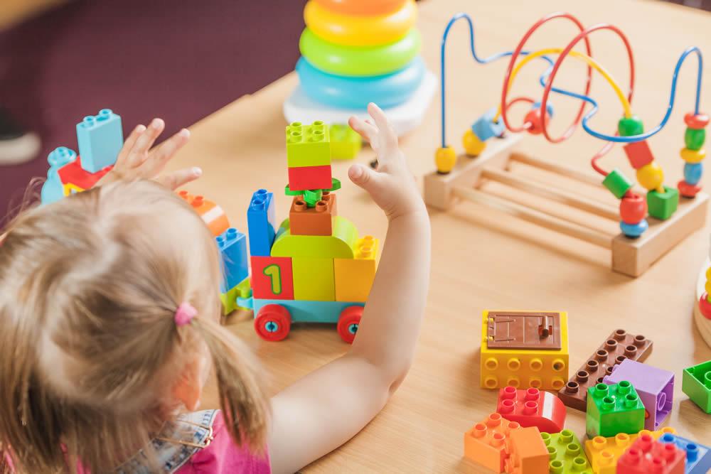 девочка за столом с развивающими игрушками
