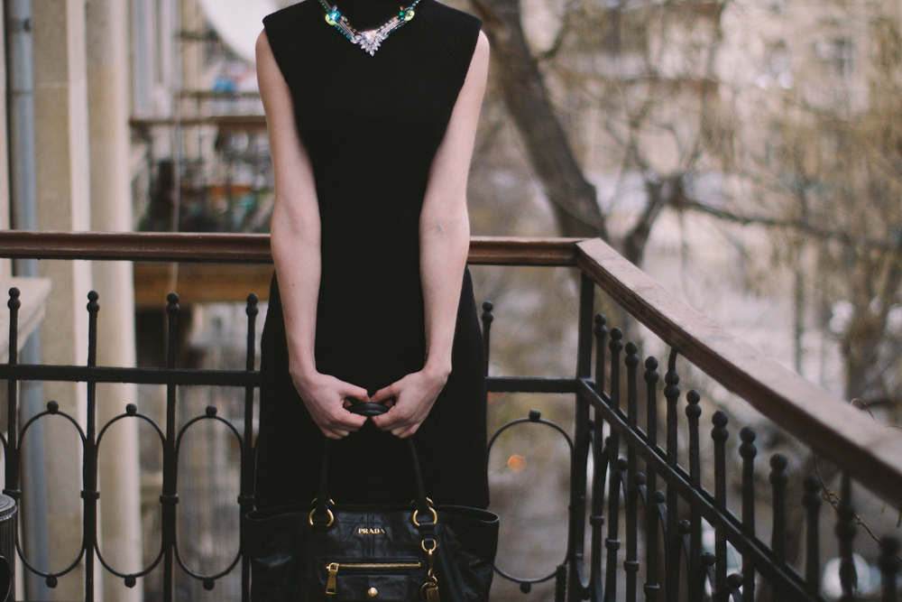 черное платье без рукавов с черной сумкой и серебряным ожерельем
