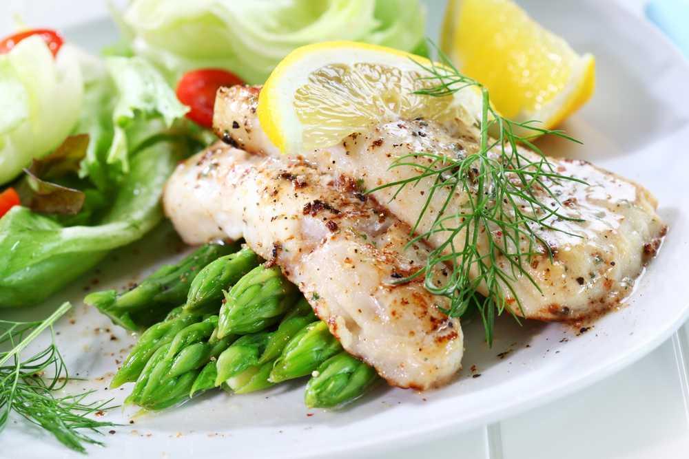 два готовых кусочка рыбы на тарелке со спаржей и лимоном