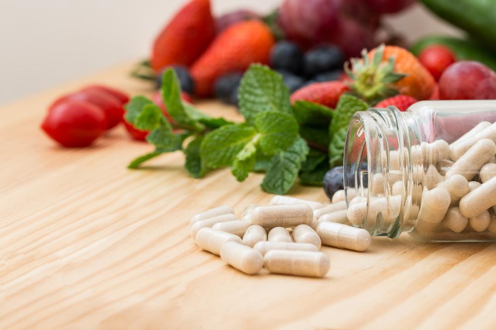 витамины в капсулах и ягоды на столе