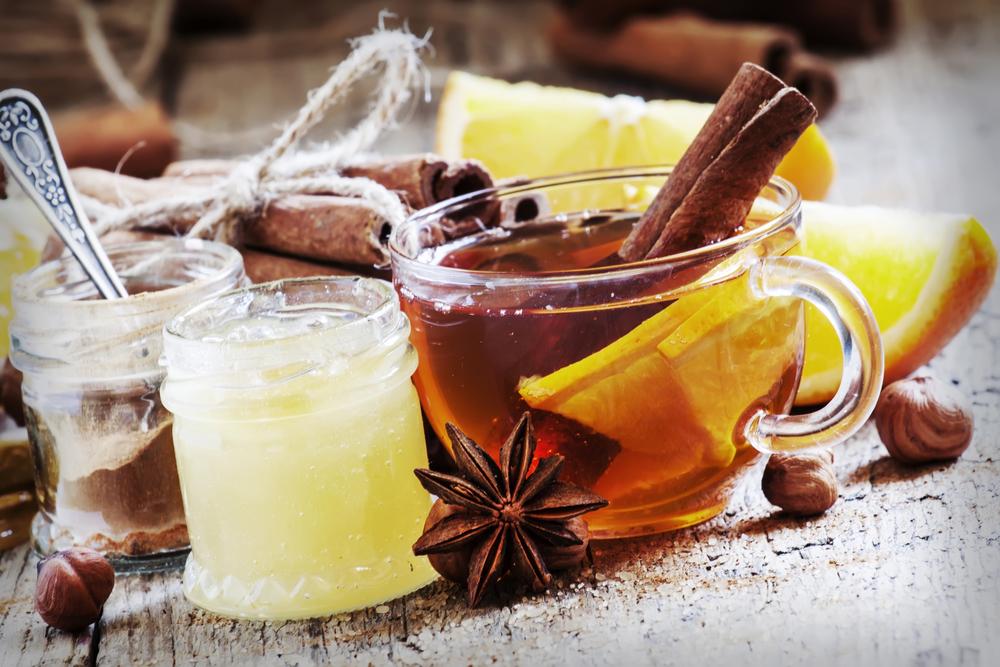 мед в банке белый и коричневый и стакан чая с лимоном и корицей
