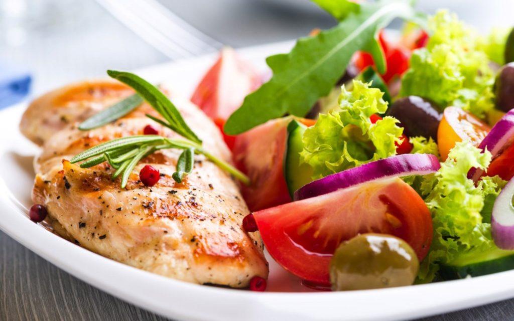 запечённая куриная грудка в тарелке с овощами и зеленью