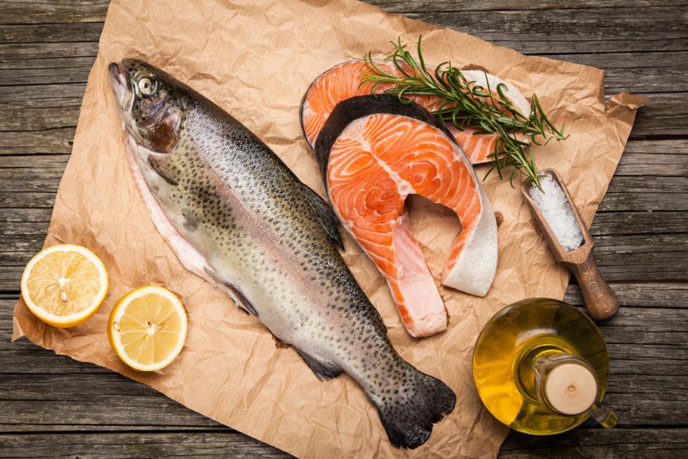 на пергаменте лежат рыба, лимон, стейки красной рыбы, ветка зелени и бутылочка масла