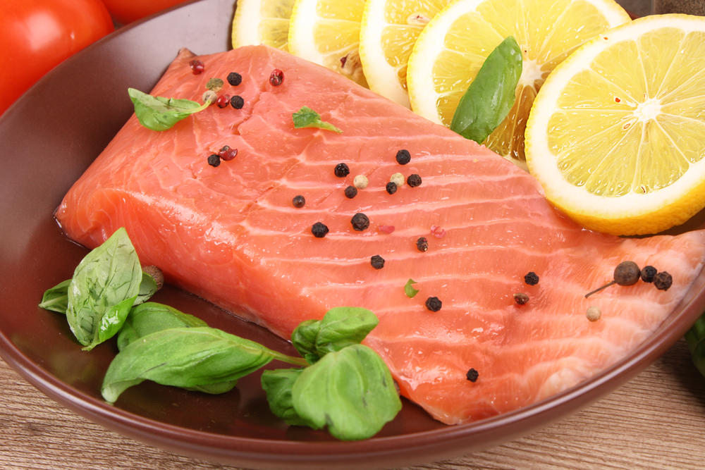 стейк красной рыбы в тарелке с дольками лимона и шпината