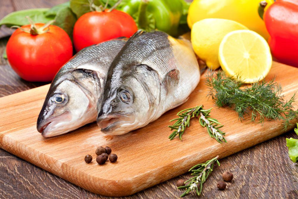 два рыбы на доске и рядом лимон, перец, помидор, укроп